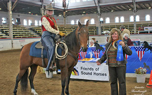 NAC 2010 - An image of a woman in coutry attire on a light brown coloured horse, Being presented with a Ribbon.