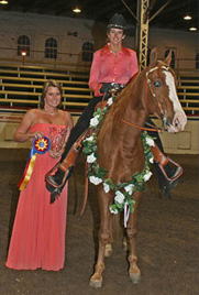 NAC 2010 - An image of a woman in a pink shirt atop a brown and white horse being presented with a ribbon.