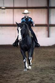 NAC 2011 - An image of a rider with a black and blue shirt atop a black horse with white spots.