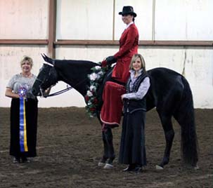 NAC 2011 - An image of a woman in red atop a black horse, Being presented a Ribbon.